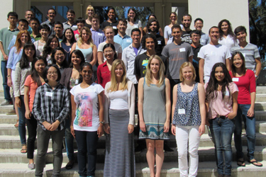 The group of incoming PhD candidates stands on the steps of Pacific Hall
