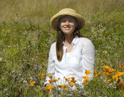 Elsa Cleland poses in a field of native Californian wildflowers, including a stand of golden poppies