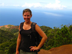 Photo of Erin, with the ocean and the top of a rainforest spread below, in the background