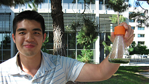 Francis Hwee holding a flask of cyanobacteria