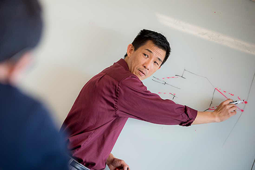 An asian man in a purple shirt points to a diagram on a whiteboard.