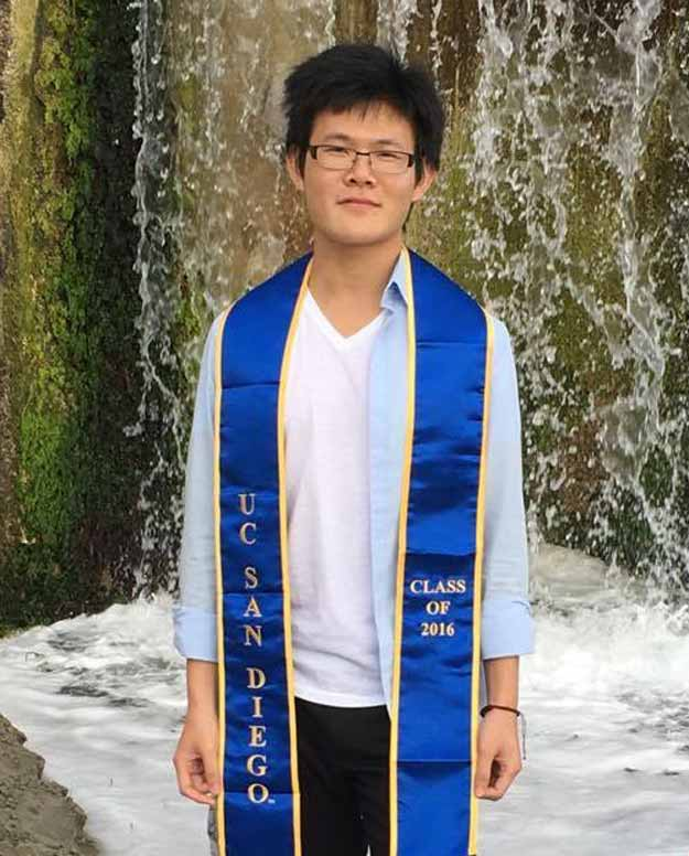 man wearing UCSD graduation stole and standing in from of waterfall