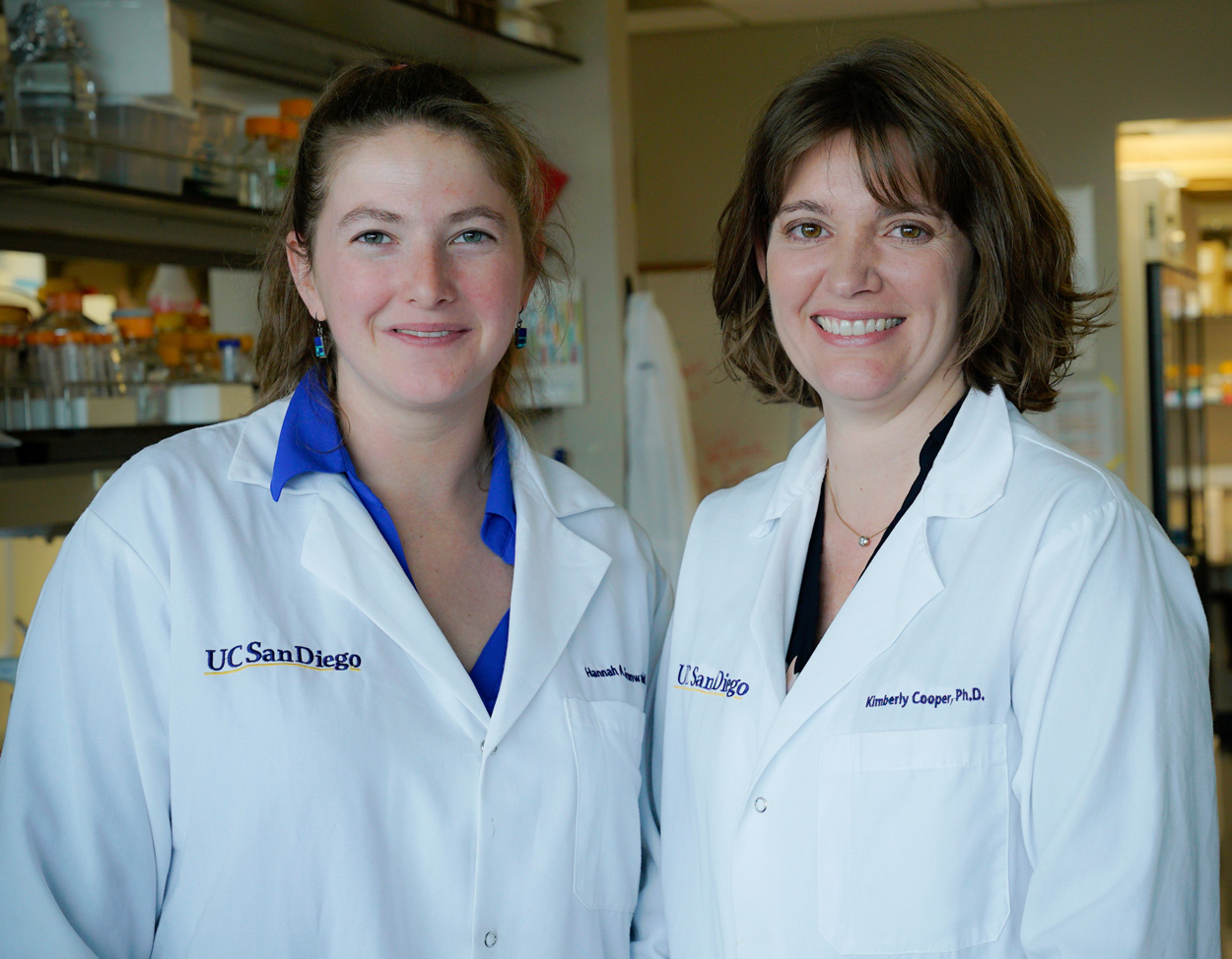 Hannah Grunwald and Assistant Professor Kimberly Cooper wearing lab coats inside Cooper's lab