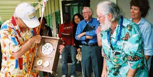 A member of Chuck's Shops crew presents him with a hand-crafted clock.
