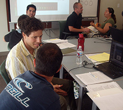 Several pairs of student and teachers in discussion and sitting around a table