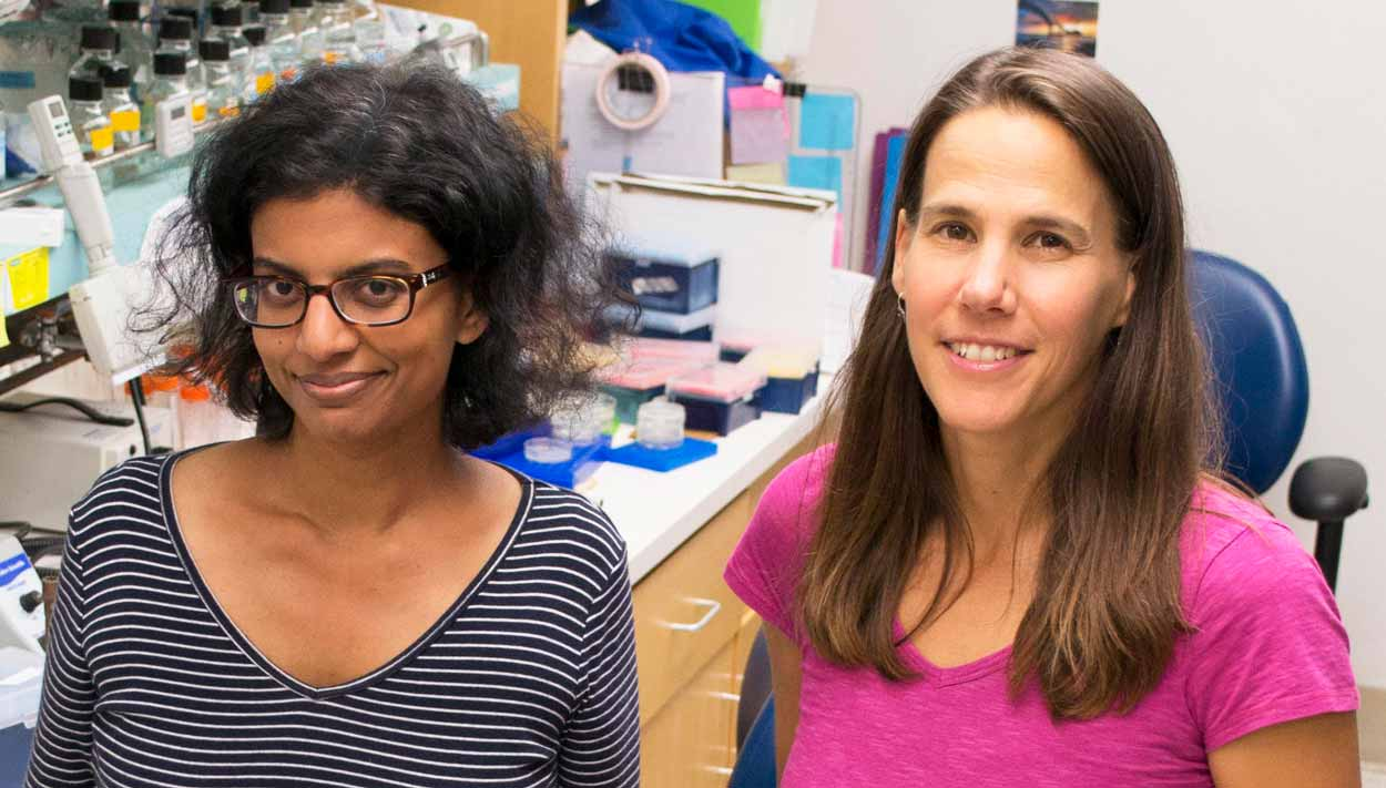 two female scientists (Reddy and Troemel) pose for a photo in the lab