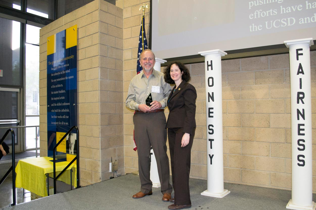Jim Posakony holding his 2018 Integrity Award and standing next to UC San Diego Executive Vice Chancellor Elizabeth Simmons onstage.